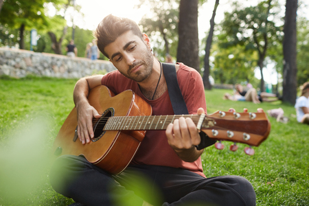Outdoor portrait of talanted man playing musical instrument and enjoying summer day. Bearded musician playing outdoors, sitting cross-legged on a grass.