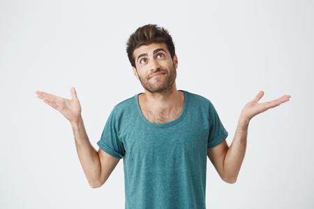 Het studioportret van knappe Spaanse kerel in blauwe doek, die bovenkant kijkt en haalt zijn schouders op die theres tonen niets hij met situatie kan doen. Gezichtsuitdrukkingen. Stockfoto