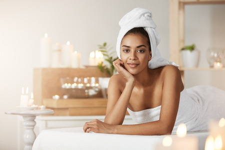 Portrait of beautiful african girl with towel on head smiling resting in spa salon. 免版税图像