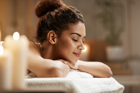 Beautiful african girl resting relaxing in spa resort with closed eyes. Stock Photo