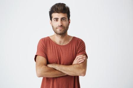 Maturo studente caucasico sorridendo dolcemente, incrociando le mani e guardando con fiducia le riprese della fotocamera per l'articolo sul suo progetto di start-up. L'uomo in maglietta rossa si sente orgoglioso e di successo Archivio Fotografico - 86637047