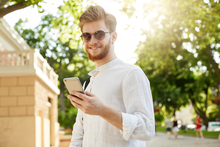 Young positive and smiling red-haired man with beard and earring in sunglasses looking through social networks on his smartphone on his way home. Stock Photo