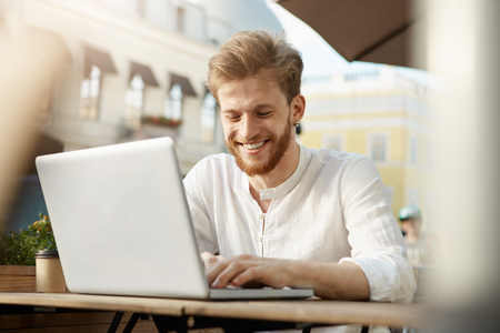 Handsome fashionable european male freelancer with trendy hair and beard sits outside in sunny weather, working on his laptop computer Stock Photo