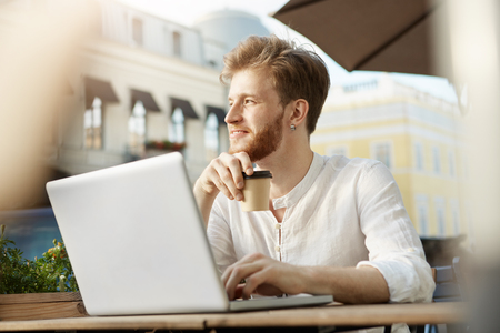 Young attractive bearded ginger guy with earring in white shirt drinks coffee, working on new project remotely on his laptop.