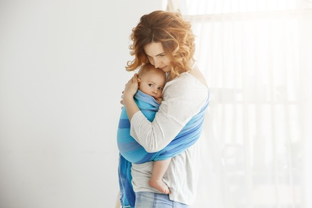 Young good-looking mother snuggles and calming her newborn son who feeling scared after long sleep interrupted by loud sounds from street. Scene of protection and love.