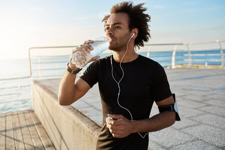 Fit afro-american male athlete drinking water out of plastic bottle after jogging on the pear in the morning. Shot of male runner in black top wearing white earphones listening to a favourite songs while doing exercises outdoors. Enjoying music and sport. Stock Photo