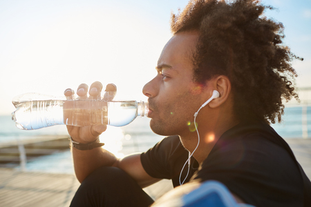 man drinking water: Outdoor shot of afro-american sportsman drinking water out of bottle in morning sunlight, wearing white earphones. Dark-skinned spotsman with bushy-hairstyle enjoying jogging in the morning by the sea. Healthy lifestyle concept.