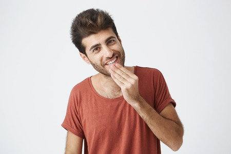 Attractive Caucasian young man pleasant looking at the camera. Cheerful and smiling, demonstrating his white teeth having good mood after getting good news