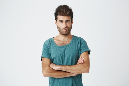 skepticism: Isolated shot of angry man wearing blue t-shirt with stylish hairstyle holding arms crossed, having skeptical and dissatisfied look. Distrust, skepticism and doubt Stock Photo