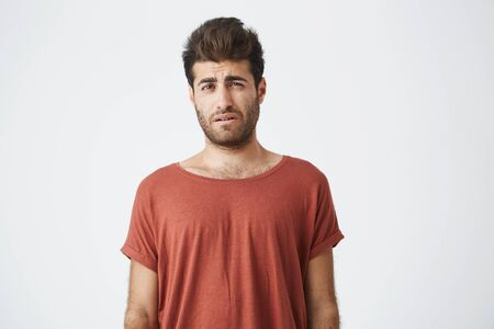Bearded stylish male having displeased look standing in casual cloth against white background. Young man having some problems looking with unsatisfaction and discontent into camera Stock Photo