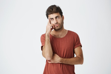 Trendy bearded young man tired of listening to somebody stories. Holding his head and rolling his eyes as he doesn't want to continue listening useless talks