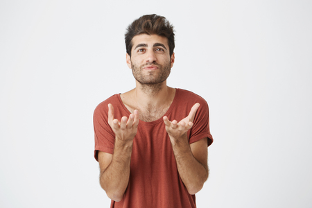 Studio portrait of attractive bearded student in red t-shirt stretching his hands to the camera. Emotional man with stylish hairstyle not understanding what is wanted from him