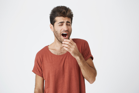 Yawning young fellow with beard and trendy hairstyle tired of work and holding his hand behind his mouth. Student wearing red T-shirt got bored of lectures Foto de archivo