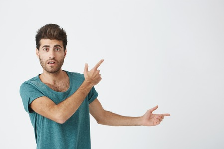 Indoor shot of astonished good-looking man dressed in casual cloth having excited fascinated look, indicating at blank studio wall with his index finger. Isolated shot, horizontal