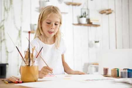 children painting: Shot of adorable blonde girl with freckles biting her tongue because of inspiration while painting. Girl with blond hair sitting at the room filled with morning light and wearing white clothes.