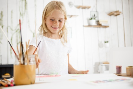 Indoor shot of beautiful blonde european girl smiling and joyfully painting picture with brush for her mother. Children and positive emotions concept.