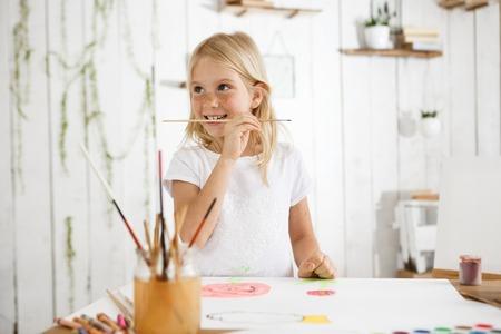 poquito: Alegre niña de siete años con cabello rubio y pecas con aspecto feliz en ropa blanca. Hermosa chica rubia capturada por un impulso creativo morder pincel. Niño en la sala de arte lleno de luz solar.