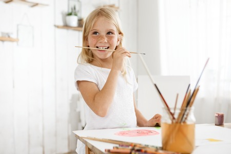 Little girl with blonde hair and freckles enjoying art wearing white t-shirt. Female child captured by a creative impulse biting brush.