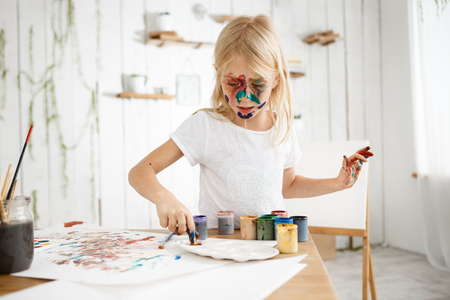 children painting: Little blonde girl busy and concentrated on mixing paint on palette. Cute and charming female kid with paint on face captured by inspiration.
