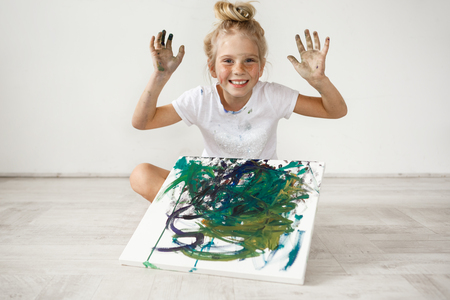 Adorable smiling Caucasian little girl with hair bun wearing white cloth holding her hands up, sitting cross-legged with colourful picture on her legs. Full of joy, cheerful blonde female kid. Stock Photo