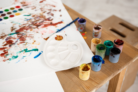 Cropped shot of wooden table with paint, brushes, palette and pictures made by children. White sheet of paper with colourdul prints of children`s palms on it.