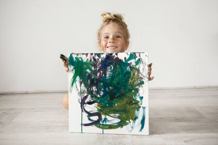 children painting: Adorable smiling little blonde girl hading by the picture. Studio shot of cute female child with hair bun and freckles posing against white wall. Childish smile is a source of positive emotions.