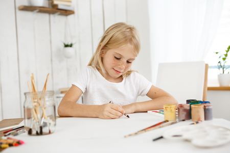 Indoor portrait of cute little blonde haired girl with freckles drawing with crayon color on the sheet of paper. Blonde child wearing white T-shirt sitting at the table drawing a picture.