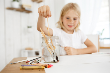 children painting: Creative and joyful blonde girl with freckles deeping brush into the water. Blonde female child painting with a brush. Kids' art activities. Stock Photo