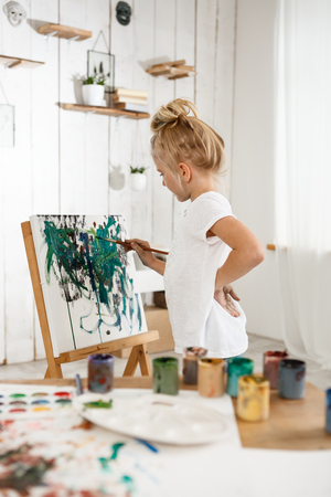 children painting: Shot of beautiful little European girl having concentrated look while working on her picture in art room. blonde female child in white t-shirt standing behind easel. Kids art activities. Stock Photo