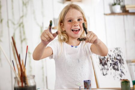 children painting: Positive and full of joy, smiling with teeth blonde european female child pointing with fingers in paint at you. Cute girl wearing white t-shirt, standing behind easel having lots of fun.