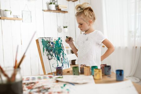 children painting: Creative, occupied female child standing behind easel, working on her new picture. Little, cute blonde girl with hair bun in white cloth enjoying art in the art room filled with sunlight. Stock Photo