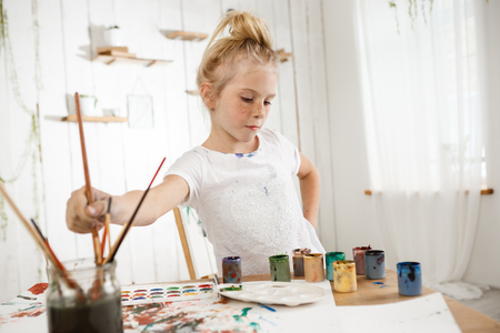 children painting: Focused on creative process cute little blond with hair bun and freckled face in white t-shirt in art room. Creative and talented female child busy with drawing, deeping brush into water, thinking about her picture.