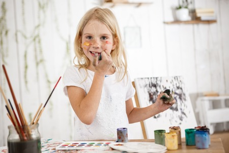Cheerful and full of joy creative little blonde smiling at the camera and touching her face with dirty hands. Female european child painting picture and enjoying art.
