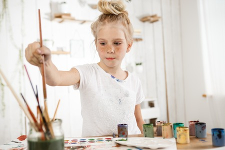 children painting: Indoor shot of European cute creative child with hair bun snd blue eyes occupied with drawing. Little blonde girl wearing white t-shirt busy with painting, deeping brush into water, drawing new masterpiece for her parents.