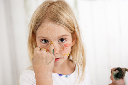 children painting: Portrait of angel-like child with colourful spots of paint on her face in white morning light in studio. Little European girl with blond hair looking attractive and balanced touching her face. Stock Photo
