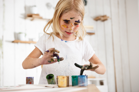 children painting: Little blond girl deeping her fingers in paint. European female child occupied with painting, wearing white t-shirt with paint spots on her face. Children and art. Stock Photo