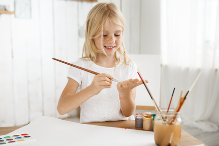 children painting: Cheerful, smiling and happy little blonde girl in white t-shirt drawing something on her palm with a brush. Eight-year-old freckled female kid standing behind desk at the art room filled with sunlight.