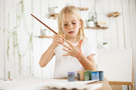 children painting: Cute, beautiful blonde girl in white t-shirt joyfully painting her palm with brush, standing behind the desk with jar of water, brushes, and paint on it. Isolated shot, horizontal.