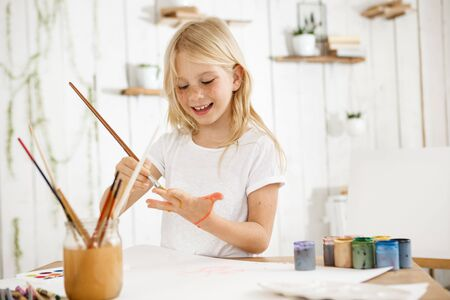 messed: Smiling with teeth and happy little blonde girl in white t-shirt drawing something on her palm with a brush. Female european child enjoying art work. Human emotions and feelings. Stock Photo