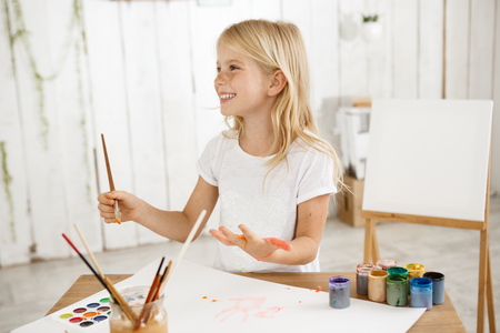 Smiling angel-like beautiful child with blonde hair wearing white t-shirt painting on her palm. Charming little girl drawing picture for her father, preparing birthday surprise for him. Children and art. Stock Photo