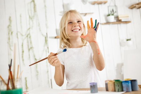 children painting: Happy and playful cute freckled blonde girl dressed in white, holding brush in one hand and showing another hand, which she messed up with paint. Children and happiness concept. Isolated shot, horizontal Stock Photo