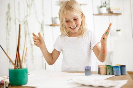 children painting: Smiling, happy and cheerful blonde girl showing her teeth, having fun while painting. Female freckled child messed up her hand with paint of different colors. Stock Photo