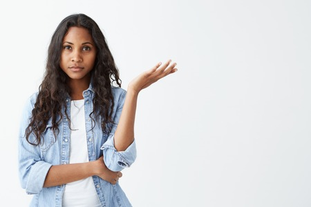 Unsure doubtful dark-skinned woman with black long wavy hair shrugging her shoulder in questioning gesture of uncertainty, having confused and dissatisfied look. Who cares Stockfoto