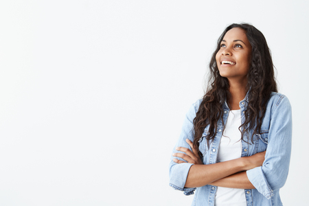 Indoor shot of beautiful happy Afro-American female employee standing isolated on white studio smiling cheerfully, keeping her arms folded, relaxing indoors after work.