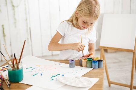 Focused and inspired little blonde girl deeping brush into paint, mixing it. Female freckled child in white t-shirt occupied with painting.