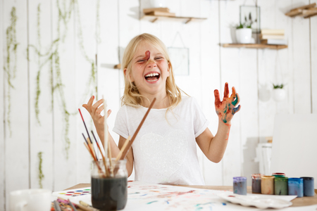 Laughing, charming little girl with blonde hair, freckles and blue eyes messed up herself with paint. Creative child with paint on her face and hands.