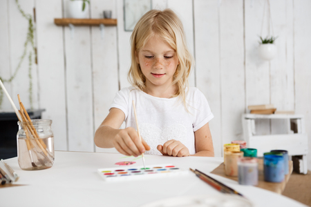 children painting: Cute and charming blonde girl wearing white tshirt deeping brush into paint. Cheerful child with freckles preparing surprise for her parents. Kids and art concept. Stock Photo