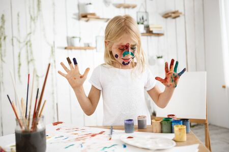 children painting: Beautiful, cute, blonde girl with painted face wearing white t-shirt drawing with her hands on white sheets of paper. Showing up her palms in paint. Kids art and fun.