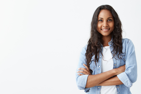 broadly: Glad young good looking Afro-American woman with clean dark skin and black long hair posing indoors with crossed arms, smiling broadly with white teeth, laughing at good joke, wearing denim shirt over white t-shirt.