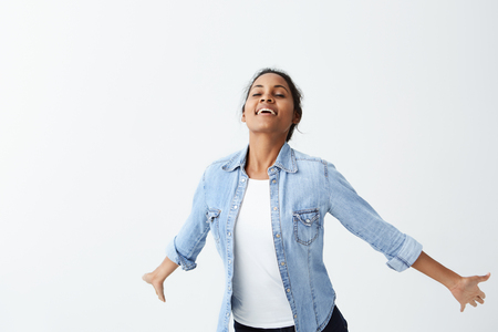 Adorable dark-skinned female in denim shirt having black hair smiling with white even teeth while jumping. People, sincere emotions, lifestyle concept
